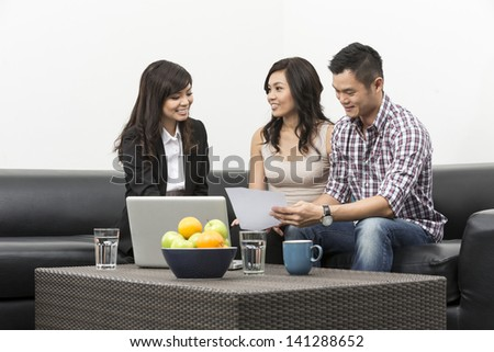 Sales Consultant showing new investment plans to young Chinese couple - stock photo