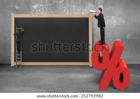 Sales man using megaphone standing on red percentage sign with blank blackboard concrete and room background - stock photo