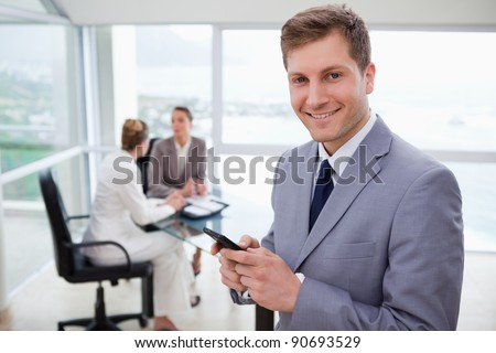 Sales manager holding cellphone with his team sitting behind him - stock photo