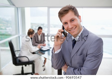 Sales manager on the phone with his team sitting behind him - stock photo