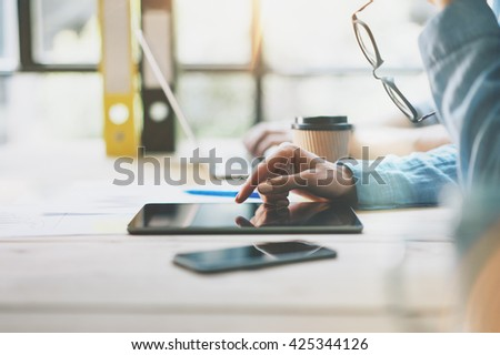 Sales Managers Team Brainstorming Process in modern office.Project Producer use Digital Tablet,holding glasses female hand.Young Business crew working New Startup studio.Blurred,film effect - stock photo