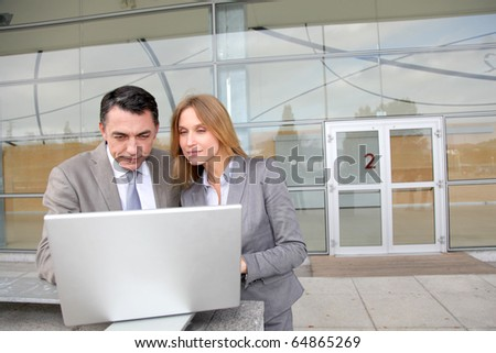 Sales people working outside modern building - stock photo