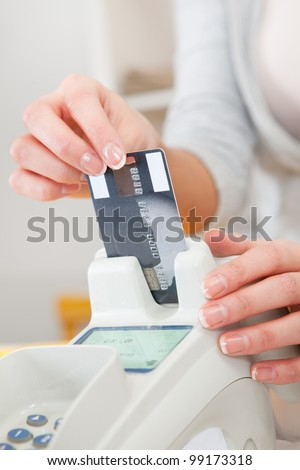 Sales person inserting credit card into scanner