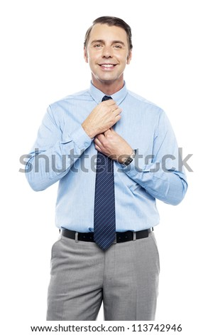 Sales representative adjusting his tie before the meeting. Looking at camera - stock photo