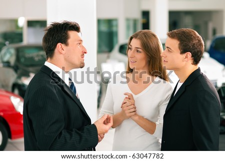Sales situation in a car dealership, the dealer is talking to a young couple, there are cars standing in the background - stock photo
