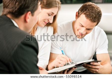Sales situation in a car dealership, the young couple is signing the sales contract to get the new car in the background - stock photo