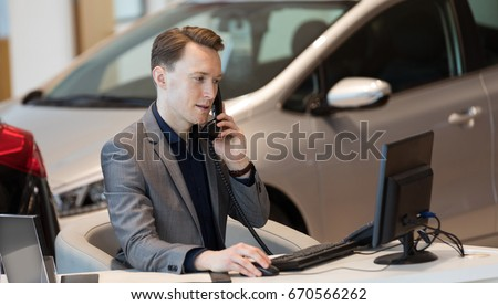 Sales talking on phone while using computer at desk in car showroom