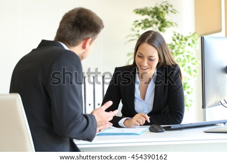 Salesclerk talking trying to convince to a happy client in a desktop at office - stock photo
