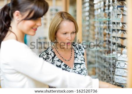 Salesgirl assisting senior woman in selecting glasses at optician store - stock photo