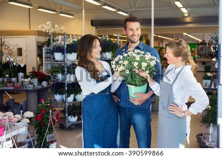 Salesgirls Assisting Male Customer In Buying Flower Plants