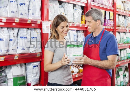 Salesman Assisting Customer In Buying Pet Food At Shop