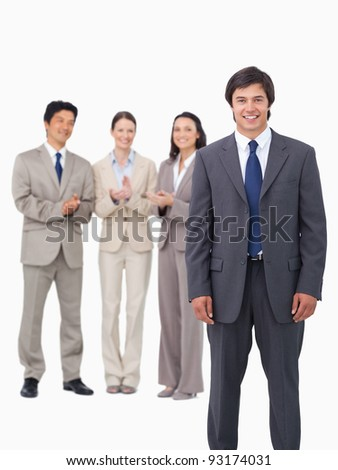 Salesman getting applause from colleagues against a white background