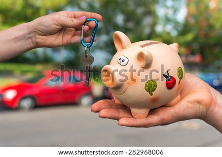 Salesman giving car key to a new car owner, who is paying last saving money from piggy bank on blurred background - stock photo