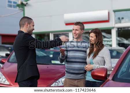 Salesman giving car keys to a couple in a dealership - stock photo