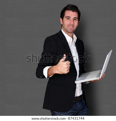 Salesman holding laptop computer and showing thumb up - stock photo
