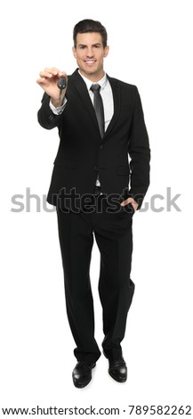 Salesman in formal suit holding car key on white background
