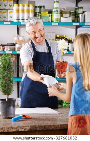 Salesman in nursery selling potting soil for an orchid to a woman - stock photo