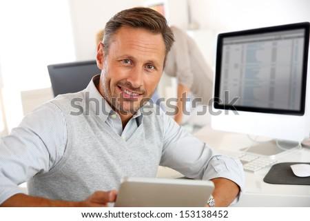 Salesman in office using digital tablet - stock photo
