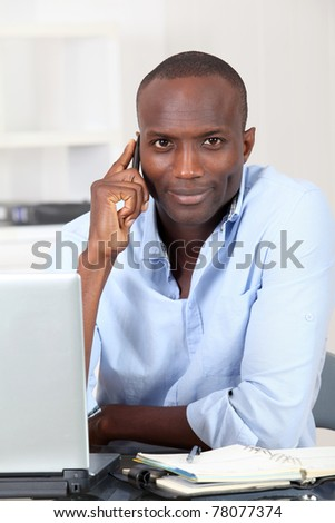 Salesman in office using mobile phone