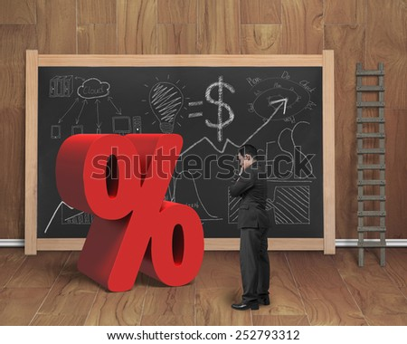 Salesman looking at red percentage sign with business concept doodles on blackboard in wooden room background - stock photo