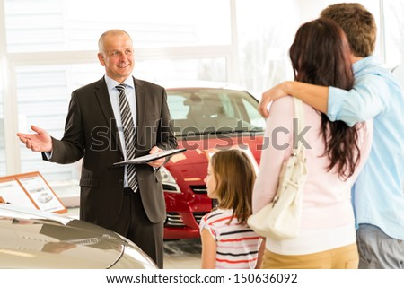 Salesman selling car to Caucasian family - stock photo