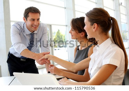 Salesman shaking hands to clients - stock photo