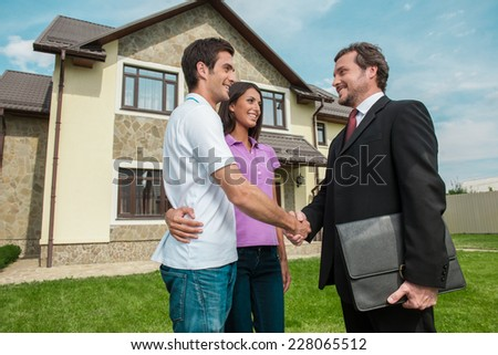 Salesman shaking hands with property owners. Handshake deal with young couple outside on lawn - stock photo