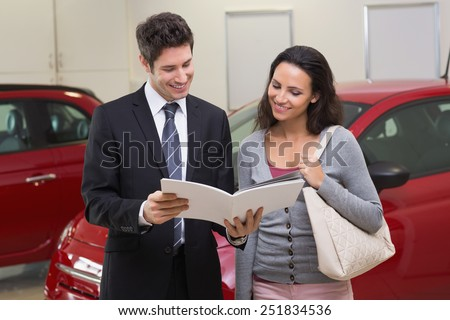Salesman showing brochure to customer and smiling at new car showroom - stock photo
