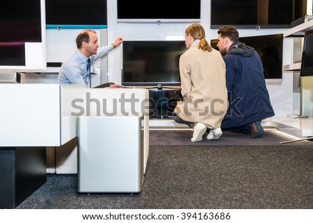 Salesman showing latest flat screen TV to couple in hypermarket - stock photo