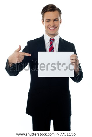 Salesman smiling and pointing towards blank billboard isolated over white