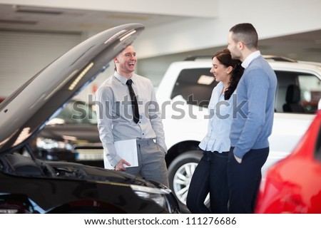 Salesman smiling as he talks to a couple in a car dealership - stock photo