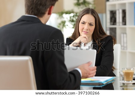 Salesman trying to convince a doubtful customer showing products in a tablet at workplace - stock photo
