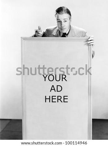 Salesman with sign saying buy now - stock photo