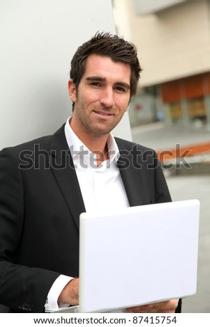 Salesman working outside on laptop computer - stock photo