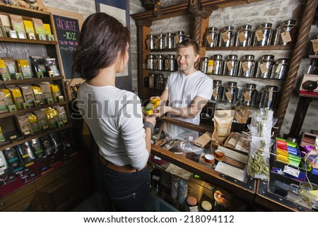 Salesperson giving product to female customer in tea store - stock photo