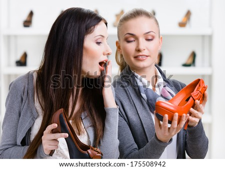Salesperson offers stylish pumps for the female customer in the shopping center - stock photo