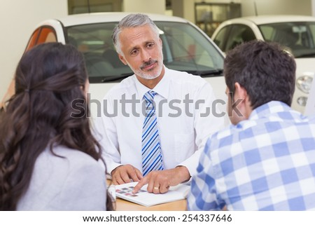 Salesperson pointing something on booklet at new car showroom - stock photo