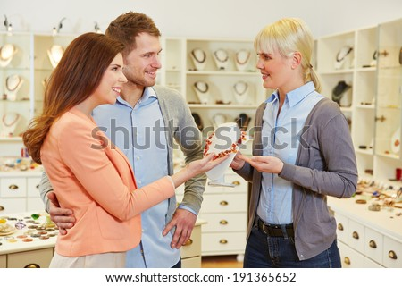 Saleswoman advising couple a happy in a jewelry store - stock photo