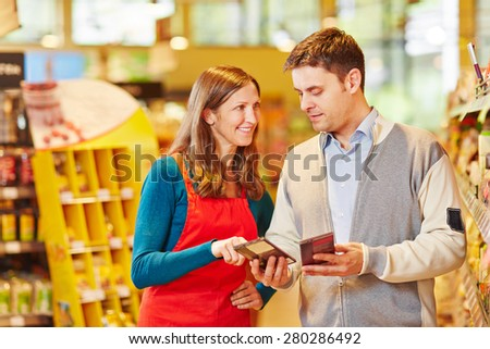 Saleswoman giving advice to man in supermarket for buying chocolate