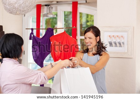Saleswoman giving shopping bags to female customer in boutique