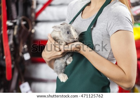 Saleswoman Holding Rabbit At Store