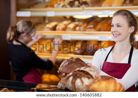 saleswoman in bakery with bread in her hands in front of shelves - stock photo