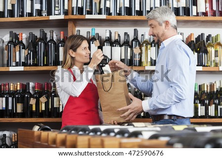 Saleswoman Putting Wine Bottle In Paperbag For Customer