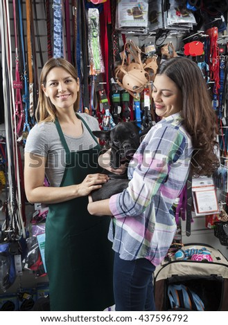 Saleswoman Standing With Female Customer Carrying French Bulldog