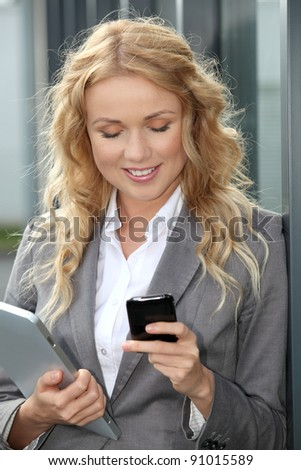 Saleswoman using mobile phone and digital tablet