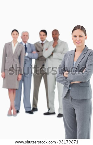 Saleswoman with arms folded and her team behind her against a white background