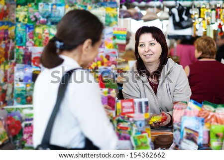saleswoman with sells seeds at garden store - stock photo