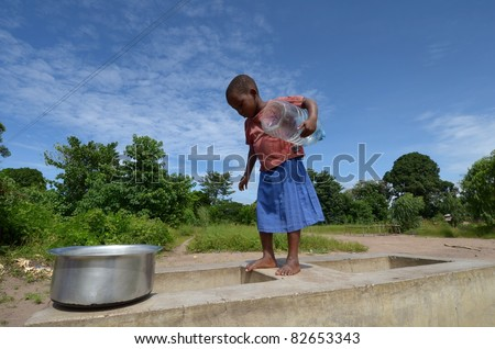 SALIMA, MALAWI-APRIL 10:African unidentified child take water far from their home, in Salima on April 10, 2011.Many children do kilometers on foot and do not attend school to help their family during drought. - stock photo