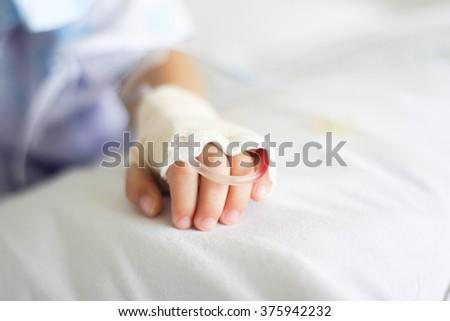 Saline intravenous (iv) drip in a Children's patient hand - stock photo