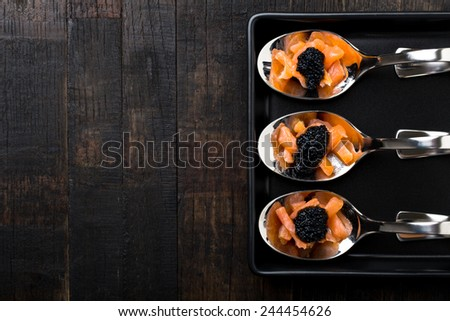 salmon and caviar on elegant silver spoons - stock photo